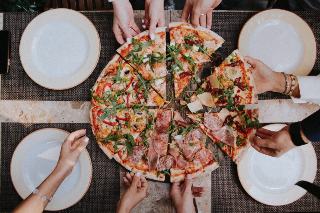 A group of friends enjoying a large pizza.